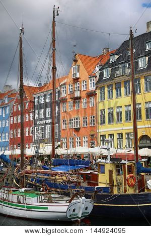 COPENHAGEN DENMARK - AUGUST 14 2016: Boats in the docks Nyhavn people restaurants and colorful architecture. Nyhavn a 17th century harbour in Copenhagen Denmark on August 14 2016.