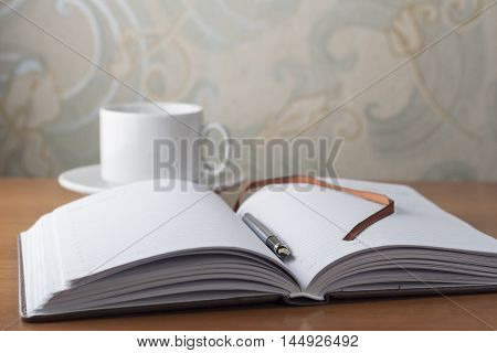 Open diary and pen businessman lying on a wooden table next to a white cup.