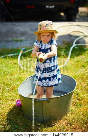 Adorable little girl playing with a water gun on hot and sunny summer evening