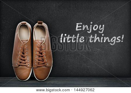 Enjoy little things text on black board and shoes
