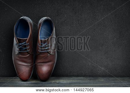 Black board and business shoes on wooden floor