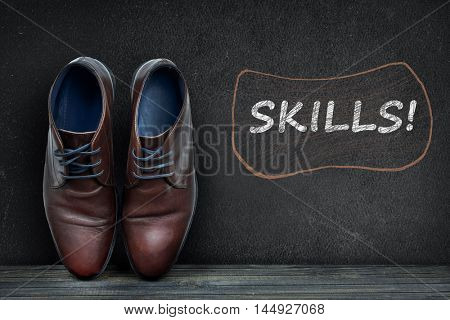 Skills text on black board and business shoes on wooden floor