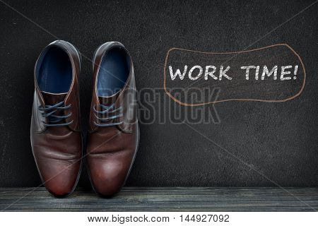 Work time text on black board and business shoes on wooden floor