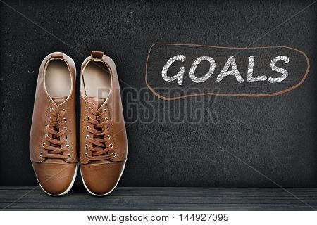 Goals text on black board and shoes