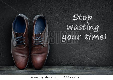 Stop wasting your time text on black board and business shoes on wooden floor