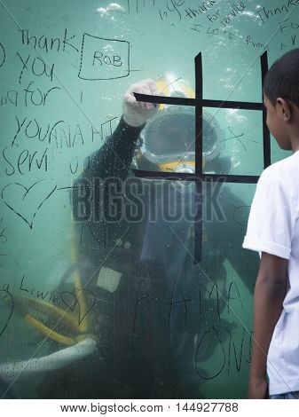 NEW YORK MAY 27 2016: An unidentified boy plays tic tac toe against a US Navy EOD technician on the glass of a 6,800 gallon mobile dive tank on Pedestrian Plaza in Times Square during Fleet Week 2016.