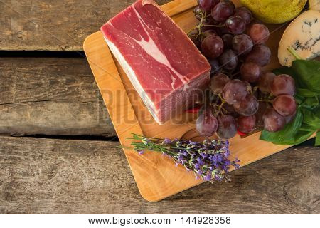 Lavender flowers and raw meat. Grapes and cheese with mold. Taste of organic food. Fresh pork for steak.