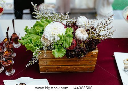 Decor of natural vegetables and fruit on a table, standing in a wooden box and decorated with flowers.