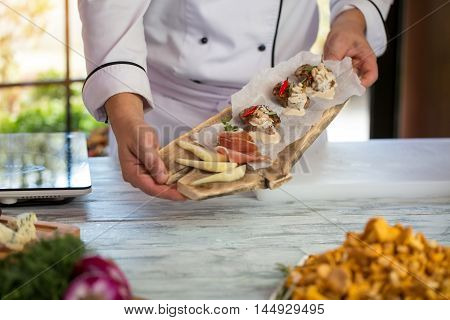 White sauce on cooked meat. Hands hold board with food. Proven recipe of beef medallions. Chef has high skills.