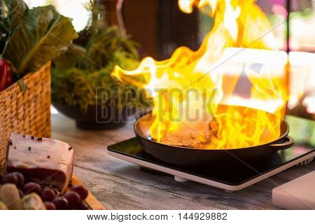 Flame in a pan. Meat and yellow fire. Special methodology of cooking. It's hot in the kitchen.