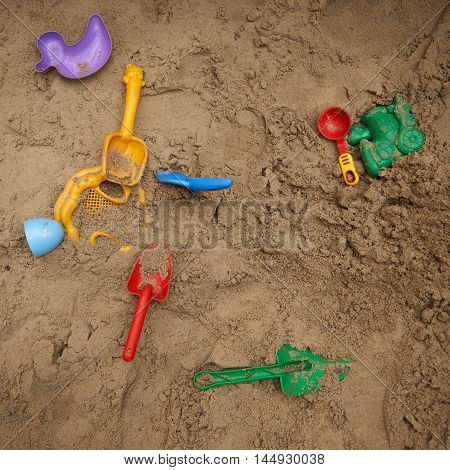 Set of color plastic toys on the sand.