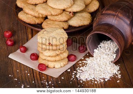 Oatmeal cookies with flakes and cherries on a wooden table