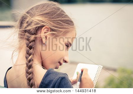 Young Girl Drawing Sketch In Notebook Near Pond