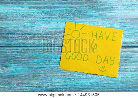 Piece of note paper on blue wooden background, have a good day