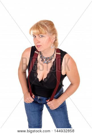 A woman in her forties standing in jeans and a black blouse with red suspenders and a necklace isolated for white background.