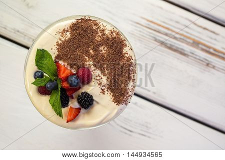 Dessert with chocolate crumbs. Blueberry and mint leaf. Top view of tiramisu. Sweet dish on wooden table.