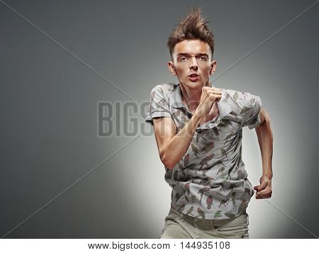 Emotional portrait of a teenager dancing on a gray background