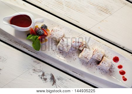 Dessert with sauce on plate. White powder on berries. Top view of berry rolls. Sweet dish with chocolate crumbs.