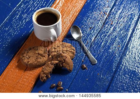 Cup of hot coffee with tasty chocolate cookies on colorful wooden table