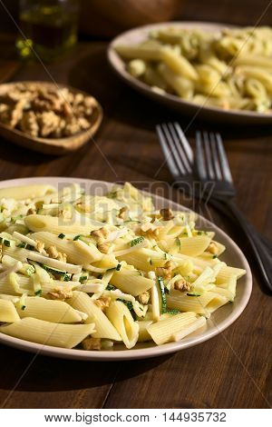 Penne pasta with zucchini and ham stripes and walnut photographed on dark wood with natural light (Selective Focus Focus in the middle of the first dish)