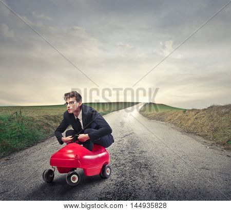 Young employee driving a toy car