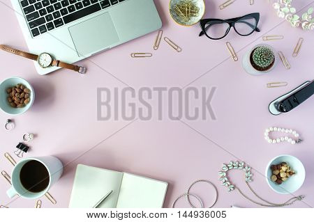 Flat lay top view office table desk frame. feminine desk workspace with succulent laptop glasses diary and golden clips on pink background.
