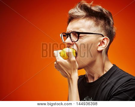 Emotional portrait of a teenager with lemon on a red background