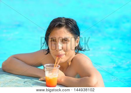Woman relaxing at the pool with cosmopolitan cocktail