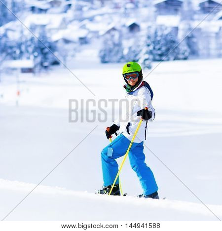 Child skiing in mountains. Active teen age kid with safety helmet goggles and poles. Ski race for young children. Winter sport for family. Kids ski lesson in alpine school. Skier racing in snow