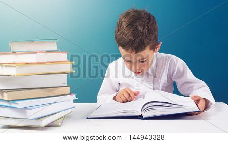 Cute boy reading book at the table blue background