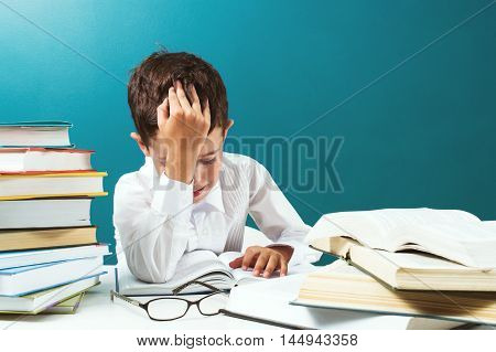 Cute boy reading difficult book at the table blue background