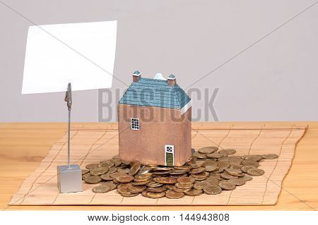 Model house on large pile of gold coins with blank white paper