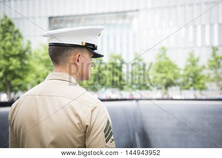 NEW YORK MAY 27 2016: US Marine looks into the reflecting pool at One World Trade after the re-enlistment and promotion ceremony held at the National September 11 Memorial site during Fleet Week 2016.