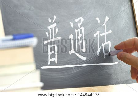 Hand writing on a blackboard in a Chinese class. Some books and school materials.