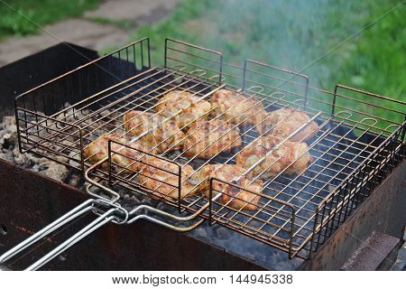 Cooking barbecue chicken thighs on hot coals.