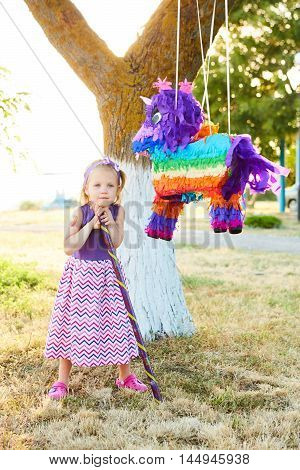 Young girl at an outdoor party hitting a pinata. Celebrating a birthday