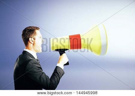 Side view of emotinal businessman screaming into megaphone on blue background. Communication concept
