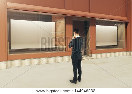 Pensive businessman looking at showcase with large billboards in daylight. Mock up 3D Rendering