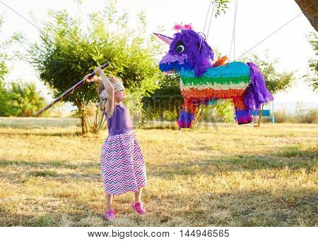 Young girl at an outdoor party hitting a unicorn pinata. Celebrating a birthday.