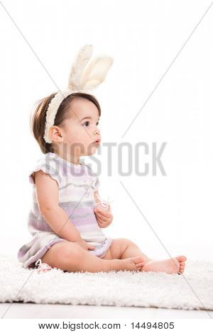 Portrait of baby girl with bunny ears headband, playing with easter eggs, isolated on white background.?