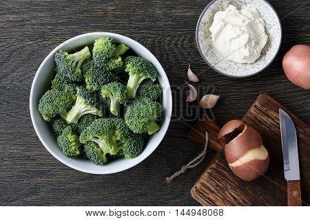A bowl with fresh broccoli cloves of garlic potatoes and cream cheese on dark wooden background. Brocoli soup ingredients.