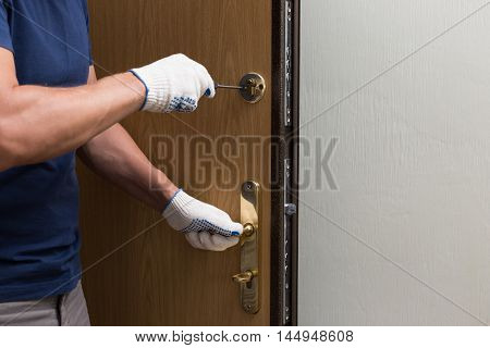 Man fixing the door with screwdriver, close up photo