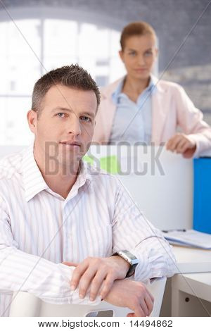 Portrait of middle-aged office worker sitting at desk, smiling, woman standing in background.?