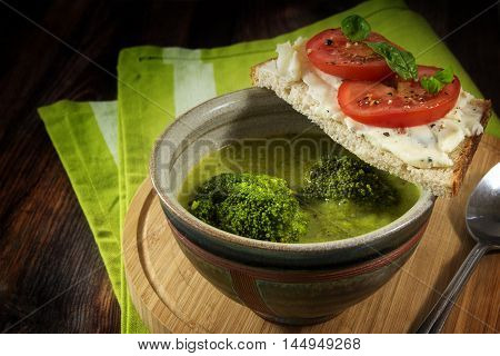homemade broccoli vegetable soup and bread with gorgonzola and tomatoes on a dark rustic wooden table with a green kitchen towel healthy vegetarian meal selected focus and narrow depth of field