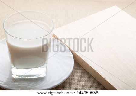 Glass Of Milk On A White Saucer On Textile Background