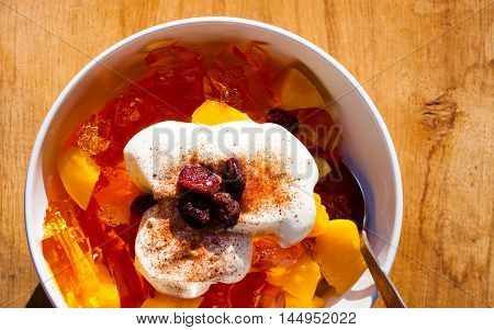 Delicious sweet jelly dessert in bowl with whipped cream and raisin cranberry on wooden table