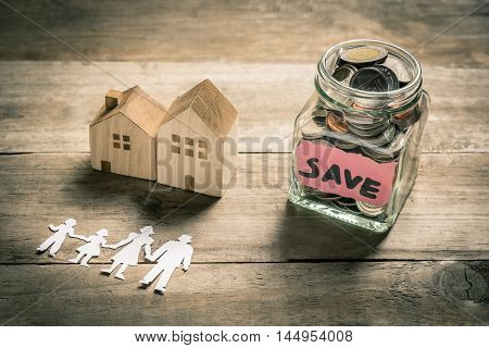 Jar of coins with paper family and wooden house. Family saving money for buying house concept
