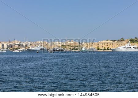 LA VALETTA MALTA - SEP 23 2012: sailing boats and yachts anchor at the old harbor in front of old town in La Valetta the capital of Malta.