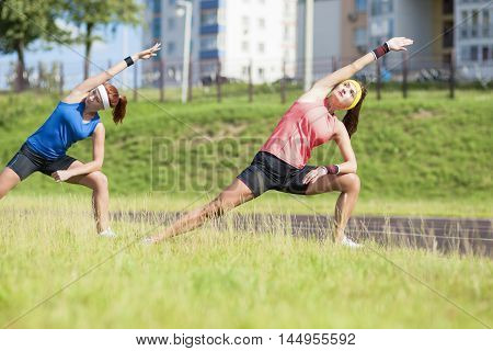 Portrait of Two Young Feale Sportswomen Having Stretching Exercises Outdoors. Horizontal Image