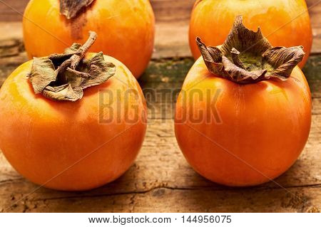 Yummy persimmon and a leaf on an old wooden table
